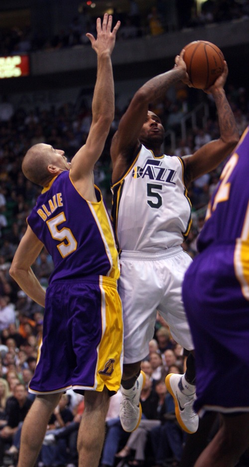 Kim Raff | The Salt Lake Tribune (right) Utah Jazz point guard Mo Williams (5) takes a jump shot as he is defended by (left) Los Angeles Lakers point guard Steve Blake (5) during a game at EnergySolutions Arena in Salt Lake City, Utah on November 7, 2012.