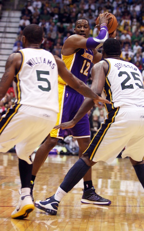Kim Raff | The Salt Lake Tribune (middle) Los Angeles Lakers center Dwight Howard (12) looks to pass the ball past (left) Utah Jazz point guard Mo Williams (5) and Utah Jazz center Al Jefferson (25) during a game at EnergySolutions Arena in Salt Lake City, Utah on November 7, 2012. Jazz went on to win the game 95-86.