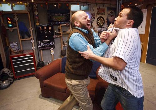 "Leah Hogsten  |  The Salt Lake Tribune Lanny Langston (in sweater) and Jesse Peery (in Yankee shirt) in Salt Lake Acting Company's ""Manning Up."""