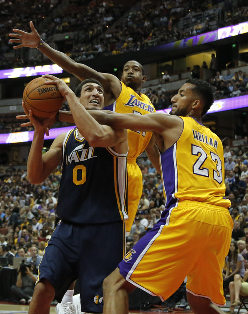Utah Jazz's Enes Kanter, left, looks to shoot as he is defended by Los Angeles Lakers' Ronnie Aguilar, left, and Chris Duhon in the second half of an NBA preseason basketball game in Anaheim, Calif., Tuesday, Oct. 16, 2012. The Jazz won 114-80. (AP Photo/Jae Hong)