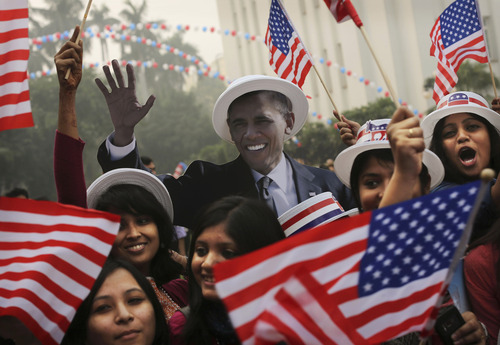 Indian students react in front of photographers next to a cardboard cutout of President Barack Obama after he was projected as the winner during an event organized by the U.S embassy at the landmark Imperial Hotel in New Delhi, India, Wednesday, Nov. 7, 2012. Obama captured a second White House term, blunting a mighty challenge by Republican Mitt Romney as Americans voted for a leader they knew over a wealthy businessman they did not. (AP Photo/Kevin Frayer)