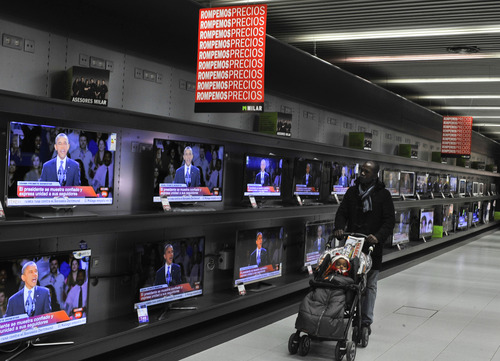 A man walks past TV screens portraying newly elected U.S. President Barack Obama, in a store in Pamplona, northern Spain, Wednesday, Nov. 7, 2012.  Obama has been re-elected President it is announced early Wedcnesday. (AP Photo/Alvaro Barrientos)