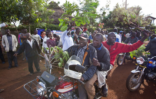 Villagers ride motorcycles and wave branches to celebrate Obama's re-election, in the village of Kogelo, home to Sarah Obama the step-grandmother of President Barack Obama, in western Kenya Wednesday, Nov. 7, 2012. (AP Photo/Ben Curtis)
