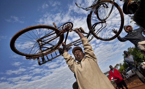 Villagers raise their bicycles in the air to celebrate Obama's re-election, in the village of Kogelo, home to Sarah Obama the step-grandmother of President Barack Obama, in western Kenya Wednesday, Nov. 7, 2012. (AP Photo/Ben Curtis)