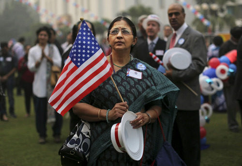 A woman wearing a sari watches during an event organized by the U.S. Embassy to mark the presidential elections at the landmark Imperial Hotel in New Delhi, India, Wednesday, Nov. 7, 2012. Obama captured a second White House term, blunting a mighty challenge by Republican Mitt Romney as Americans voted for a leader they knew over a wealthy businessman they did not. (AP Photo/Kevin Frayer)