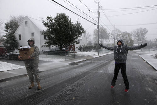Volunteer Karina Ayubi does jumping jacks to keep warm while waiting for National Guardsmen to unload blankets donated by the American Red Cross as a nor'easter approached in the wake of Superstorm Sandy, Wednesday, Nov. 7, 2012, in Little Ferry, N.J. (AP Photo/Kathy Willens)