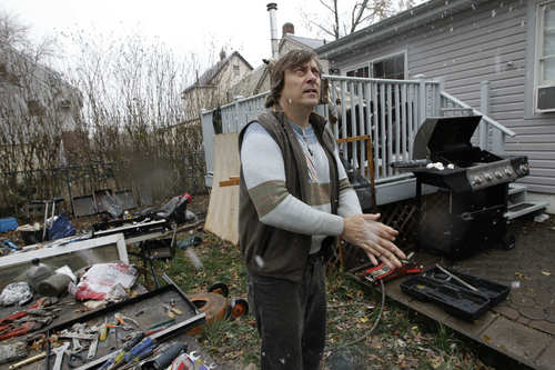 Frank Hlavaty rubs his hands together for warmth as he eyes a fallen tree next door to his house, flooded by Superstorm Sandy, as a nor'easter approached, Wednesday, Nov. 7, 2012, in Little Ferry, N.J. (AP Photo/Kathy Willens)
