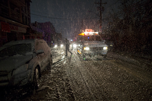 A New York Police Department van broadcasts the location of warm shelters over a loudspeaker as snow as it accumulates in the Rockaway Park neighborhood of the borough of Queens, New York, Wednesday, Nov. 7, 2012, in the wake of Superstorm Sandy. A Noreaster is complicating an already difficult situation with wind and blowing snow. (AP Photo/Craig Ruttle)