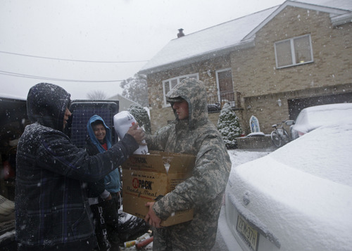 National Guardsman Brandon Kyle, right, hands out blankets  donated by the American Red Cross to workers helping a resident clean up his flooded house as snow fell from a Noreaster that approached in the wake of Superstorm Sandy, Wednesday, Nov. 7, 2012, in Little Ferry, N.J. (AP Photo/Kathy Willens)