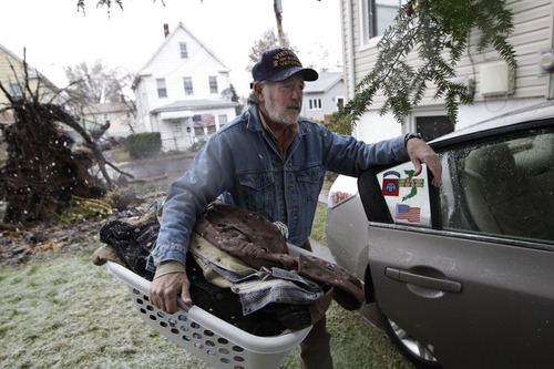Leonard Hekel loads a basket of clothing into his car after deciding to temporarily move out of his house which was flooded by Sandy and still had no power as a Noreaster approached, Wednesday, Nov. 7, 2012, in Little Ferry, N.J. (AP Photo/Kathy Willens)