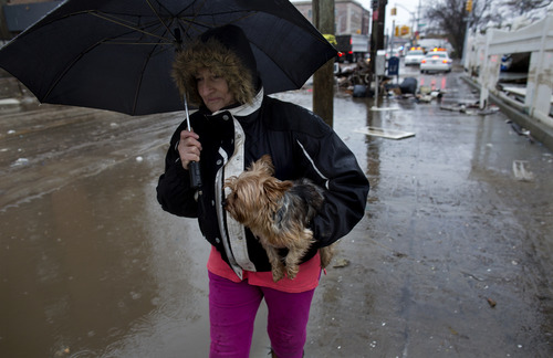 Helena Hamilec, of the Rockaway Beach neighborhood of the borough of Queens, New York, Wednesday, walks though her neighborhood where debris that still litters the streets Wednesday, Nov. 7, 2012, in the wake of Superstorm Sandy. A nor'easter is complicating an already difficult situation with wind, rain and snow. (AP Photo/Craig Ruttle)