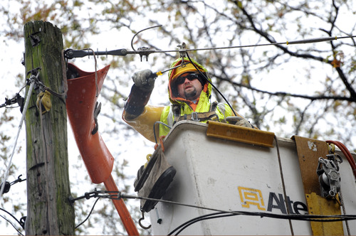 Rick Foite, a lineman with Harlan Electrical Construction from Buffalo, N.Y. repairs power lines that were brought down from the effects of Superstorm Sandy on Wednesday, Nov. 7, 2012, in Sea Cliff, N.Y. (AP Photo/Kathy Kmonicek)