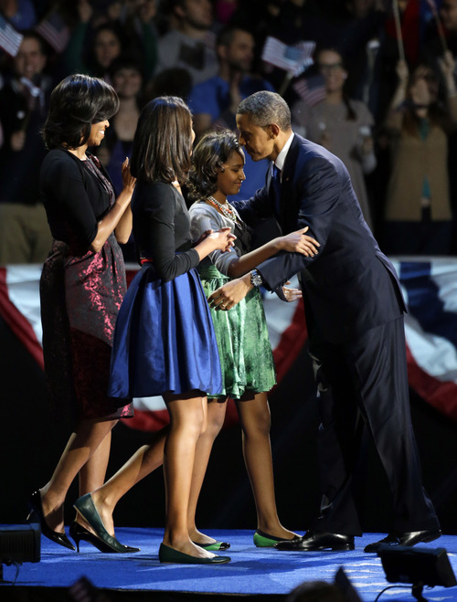 President Barack Obama hugs his daugher Sasha after his speech as his wife Michelle and daughter Malia gather on stage at his election night party Wednesday, Nov. 7, 2012, in Chicago. President Obama defeated Republican challenger former Massachusetts Gov. Mitt Romney. (AP Photo/Pablo Martinez Monsivais)