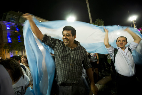 Protesters waving an Argentine flag demonstrate during a march against Argentina's President Cristina Fernandez in Buenos Aires, Argentina, Thursday, Nov. 8, 2012. Angered by rising inflation, violent crime and high-profile corruption, and afraid Fernandez will try to hold onto power indefinitely by ending constitutional term limits, the protesters banged pots and marched in Argentina's capital. Protests also were held in plazas nationwide and outside Argentine embassies and consulates around the world. (AP Photo/Victor R. Caivano)