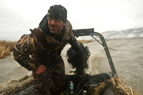 Chris Detrick  |  The Salt Lake Tribune  Carl Taylor pilots his boat while duck hunting with his dog JB in Farmington Bay Tuesday November 23, 2010.