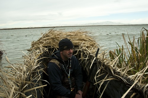 Chris Detrick  |  The Salt Lake Tribune  Carl Taylor waits in his boat while duck hunting with his dog JB in Farmington Bay in 2010.