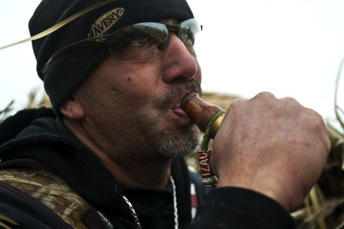 Chris Detrick  |  The Salt Lake Tribune  Carl Taylor blows in a duck call while duck hunting with his dog JB in Farmington Bay Tuesday November 23, 2010.