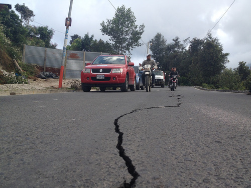 Residents on motorcycles drive past a damaged road after a magnitude 7.4 earthquake struck in San Marcos, Guatemala, Wednesday, Nov. 7, 2012. The mountain village, some 80 miles (130 kilometers) from the epicenter, suffered much of the damage with some 30 homes collapsing in its center. There are three confirmed dead and many missing after the strongest earthquake to hit Guatemala since a deadly 1976 quake that killed 23,000. (AP Photo/Moises Castillo)