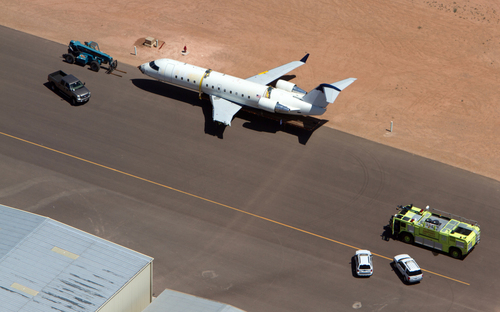 A SkyWest regional jet sits on the tarmac on the opposite end of the St. George Municipal Airport Tuesday, July 17, 2012.  A SkyWest Airlines employee wanted in a murder case attempted to steal a passenger plane, then shot himself in the head after crashing the aircraft in a nearby parking lot, officials said Tuesday. Brian Hedglin, 40, scaled a razor wire fence at the St. George Municipal Airport early Tuesday, then boarded the 50-passenger SkyWest jet while the airport was closed, St. George city spokesman Marc Mortenson said.  (AP Photo/The Spectrum, Jud Burkett) NO SALES