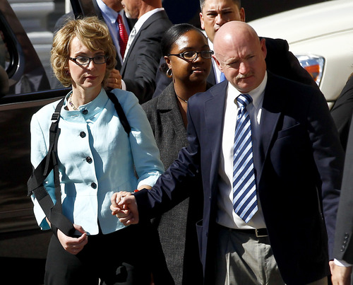 Former Democratic Rep. Gabrielle Giffords, left, and her husband Mark Kelly leave after the sentencing of Jared Loughner, in back of U.S. District Court Thursday, Nov. 8, 2012, in Tucson, Ariz.   U.S. District Judge Larry Burns sentenced Jared Lee Loughner, 24, to life in prison, for the January 2011 attack that left six people dead and Giffords and others wounded. Loughner pleaded guilty to federal charges under an agreement that guarantees he will spend the rest of his life in prison without the possibility of parole. (AP Photo/Ross D. Franklin)