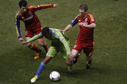 Real Salt Lake defender Tony Beltran (2) and Real Salt Lake midfielder Will Johnson (8) and Seattle Sounders FC midfielder Mario Martinez (15) during the first half of  an MLS playoff game  at Rio Tinto Stadium in Sandy, Utah, Thursday Nov. 8, 2012.  (AP Photo/The Salt Lake Tribune, Chris Detrick)