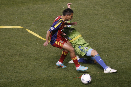 Real Salt Lake forward Paulo Junior (23) is defended by Seattle Sounders FC defender Jeff Parke (31) during the first half of the Major League Soccer playoff game at Rio Tinto Stadium Thursday Nov. 8, 2012. (AP Photo/The Salt Lake Tribune, Chris Detrick)