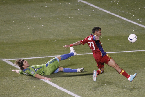 Real Salt Lake forward Paulo Junior (23) kicks around Seattle Sounders FC midfielder Steve Zakuani (11) during the first half of the Major League Soccer playoff game at Rio Tinto Stadium Thursday  Nov. 8, 2012. (AP Photo/The Salt Lake Tribune, Chris Detrick)
