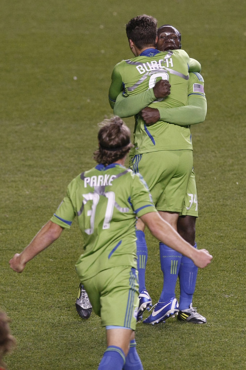 Seattle Sounders FC defender Jeff Parke (31) Seattle Sounders FC defender Marc Burch (8) and Seattle Sounders FC defender Jhon Kennedy Hurtado (34) celebrate after the Major League Soccer playoff game at Rio Tinto Stadium Thursday  Nov. 8, 2012. (AP Photo/The Salt Lake Tribune, Chris Detrick)