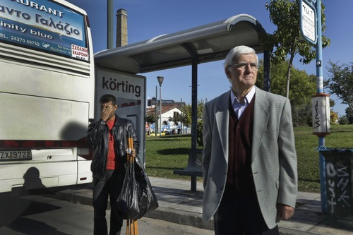 People wait for the bus, the only form of public transportation that was operating during a strike of the metro and tram networks, at a bus stop in central Athens, Friday, Nov. 9, 2012. Cash-strapped Greece will issue short term debt on Tuesday in the hope of raising enough money to repay a key bond days later. Greece is not expected to get its next batch of international rescue loans by Nov. 16, when it has to roll over euro5 billion in three-month treasury bills. (AP Photo/Lefteris Pitarakis)