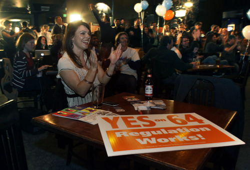FILE - In this Tuesday, Nov. 6, 2012 file photo, Amanda Jetter celebrates along with others attending an Amendment 64 watch party in a bar after a local television station announced the marijuana amendment's passage, in Denver. Votes this week by Colorado and Washington to allow adult marijuana possession have prompted what could be a turning point in the nation's conflicted and confusing war on drugs. (AP Photo/Brennan Linsley, File)