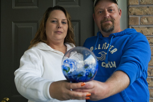 "Chris Detrick  |  The Salt Lake Tribune Shaun and Jennifer Peterson hold a memorial glass at their home Thursday November 8, 2012. Jennifer went to a Deseret Industries a few days ago and picked up a blown glass piece for $3. When she went to the Internet to find out its value, she realized it's a ""memorial glass,"" where someone's ashes are mixed into a glass piece. She's hoping to find the rightful owner who inadvertently gave away their family member."