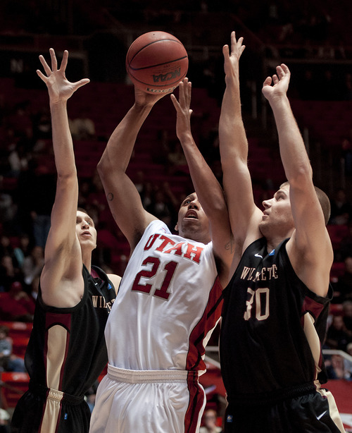 Michael Mangum  |  Special to the Tribune  Utah forward Jordan Loveridge (21) goes up for a shot with pressure from Willamette Bearcats forward Kyle McNally (4), left, and forward Alex Brown (30) during their game at the Huntsman Center on Friday, November 9, 2012. Loveridge led the team with 10 rebounds and 18 points as the Utes beat the Bearcats 104-47.