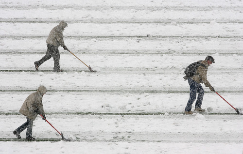 Steve Griffin | The Salt Lake Tribune   Grounds crew members try to keep the yardage lines clear of snow during the 4A semifinal football game between Highland and Mountain Crest at Rice Eccles Stadium in Salt Lake CIty, Utah Friday November 9, 2012.
