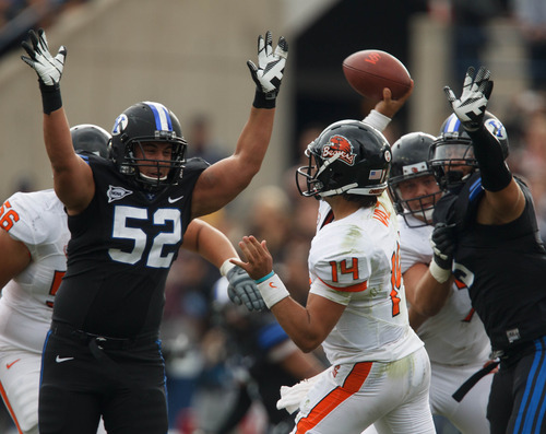 Trent Nelson     The Salt Lake Tribune BYU's Russell Tialavea (52) and Kyle Van Noy close in on Oregon State's Cody Vaz as BYU hosts Oregon State college football Saturday October 13, 2012 in Provo, Utah.