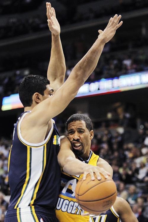 Denver Nuggets point guard Andre Miller (24) slams into Utah Jazz center Enes Kanter (0) during the first quarter of an NBA basketball game, Friday, Nov. 9, 2012, in Denver. (AP Photo/Barry Gutierrez)