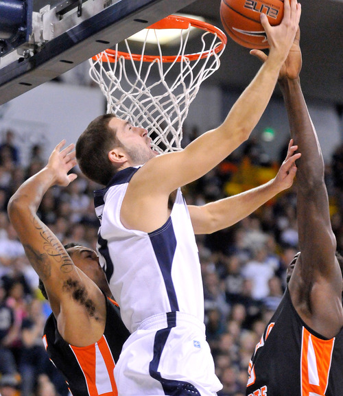 Utah State's Preston Medlin, center, goes up for a shot against two Idaho State deffenders during an NCAA college basketball game on Saturday, Nov. 10, 2012, in Logan, Utah. (AP Photo/The Herald Journal, John Zsiray)