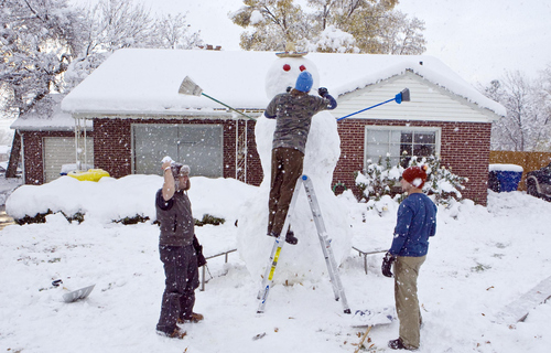 Keith Johnson |  The Salt Lake Tribune Curtis Pasin stands on a ladder as he, Ryan Evans, right, and Kevin Howard put the final touches on an 11-foot snowman they built over five hours in the front yard of their Millcreek home, November 10, 2012. The three used a long wooden plank to roll the heavy upper sections into place.