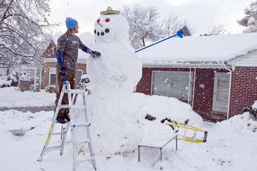 Keith Johnson | The Salt Lake Tribune Curtis Pasin stands on a ladder to put the final touches on an 11-foot snowman he and friends Ryan Evans and Kevin Howard built over five hours in the front yard of their Millcreek home, November 10, 2012. The three used a long wooden plank to roll the heavy upper sections into place.