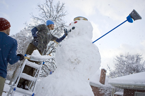 Keith Johnson |  The Salt Lake Tribune Curtis Pasin stands on a ladder as he and Ryan Evans put the final touches on an 11-foot snowman they built over five hours in the front yard of their Millcreek home, November 10, 2012. Curtis and Ryan, along with Kevin Howard (not pictured), used a long wooden plank to roll the heavy top two sections into place.