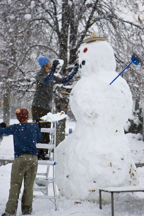 Keith Johnson |  The Salt Lake Tribune Curtis Pasin stands on a ladder as he and Ryan Evans put the final touches on an 11-foot snowman they built over five hours in the front yard of their Millcreek home, November 10, 2012. Curtis and Ryan, along with Kevin Howard (not pictured), used a long wooden plank to roll the heavy upper sections into place.
