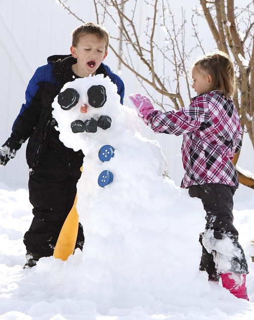 Leah Hogsten  |  The Salt Lake Tribune Callen Clarke, 7, and his sister Allie, 5, chew snow and spit it onto their snowman to make it stronger in Stansbury Park, Saturday, November 10, 2012. Scattered snowfall is expected to continue throughout Saturday, with increasing lake-effect accumulations stretching into the evening in areas south and east of the Great Salt Lake, piling on four to five more inches by Sunday morning.
