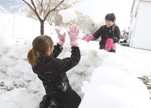 Leah Hogsten  |  The Salt Lake Tribune Sisters Madison Peterson, 10, and Elsa Peterson, 9, take a break from building a fort with their mother to lob chunks of snow at each other in Stansbury Park, Saturday, November 10, 2012. Scattered snowfall is expected to continue throughout Saturday, with increasing lake-effect accumulations stretching into the evening in areas south and east of the Great Salt Lake, piling on four to five more inches by Sunday morning.