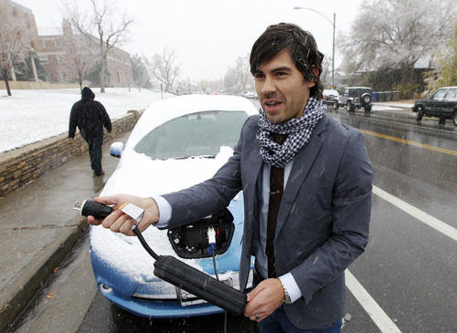 Al Hartmann  |  The Salt Lake Tribune First-year law student Rodrigo Sagebin holds the 120 volt plug in charger for is Nissan Leaf electric car.  He is one of the first University of Utah  students to drive an electric car, but the university is taking no steps to accommodate early adopters of this green technology, nor will officials allow him to charge it at the student apartments where he lives.