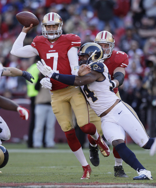 San Francisco 49ers quarterback Colin Kaepernick, left, is hit by St. Louis Rams defensive end Robert Quinn, right, during the fourth quarter of an NFL football game in San Francisco, Sunday, Nov. 11, 2012. (AP Photo/Jeff Chiu)