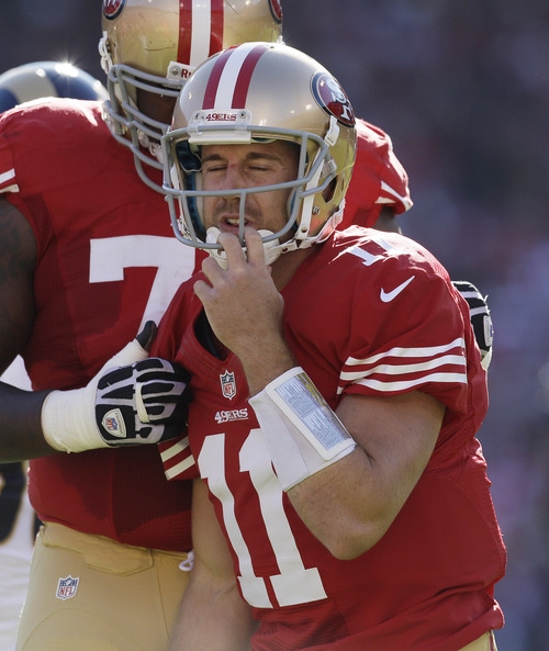 San Francisco 49ers quarterback Alex Smith slowly gets up after being hit during the first quarter of an NFL football game against the St. Louis Rams in San Francisco, Sunday, Nov. 11, 2012. In the background is San Francisco 49ers tackle Anthony Davis. Smith later left the game. (AP Photo/Jeff Chiu)