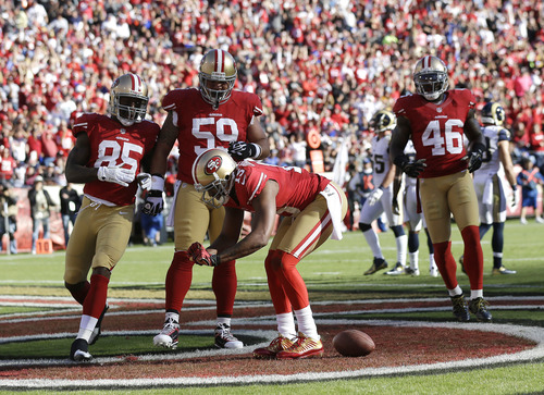 San Francisco 49ers wide receiver Michael Crabtree bends to celebrate after scoring a touchdown on a14-yard reception during the first quarter of an NFL football game against the St. Louis Rams in San Francisco, Sunday, Nov. 11, 2012. From left, is the 49ers Vernon Davis, Jonathan Goodwin, and Delanie Walker.(AP Photo/Marcio Jose Sanchez)