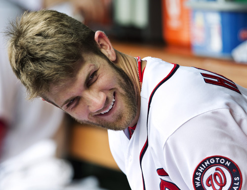 FILE - In this Oct. 3, 2012, file photo, Washington Nationals' Bryce Harper smiles as he sits in the dugout during a baseball game against the Philadelphia Phillies in Washington. Harper was named the National League Rookie of the Year Monday, Nov. 12. (AP Photo/Manuel Balce Ceneta, File)