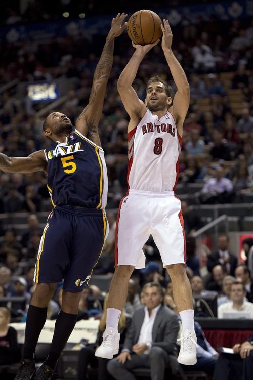 Toronto Raptors guard Jose Calderon (8) shoots past Utah Jazz guard Mo Williams (5) during the first half of an NBA basketball game, Monday, Nov. 12, 2012, in Toronto. (AP Photo/The Canadian Press, Frank Gunn)