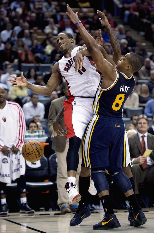 Toronto Raptors guard DeMar DeRozan loses the ball as he is fouled by Utah Jazz guard Randy Foye, right, during an NBA basketball game in Toronto on Monday, Nov. 12, 2012. (AP Photo/The Canadian Press, Frank Gunn)