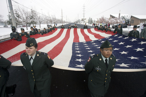 Kim Raff  |  The Salt Lake Tribune The Salt Lake East High Corps of Cadet carries a giant American flag during the Veterans Day Parade Sunday.